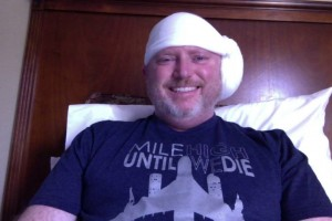 "After spending 23 hours in an ICU room, I was discharged from the hospital and sent ""home"" to our hotel. Here I am modeling my awesome head bandage and a roller derby t-shirt."